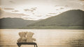 Teddybears relaxing embracing while overlooking a lake and mountains shot from behind Royalty Free Stock Images