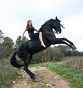 Teen and black horse Royalty Free Stock Photography