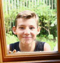 Teen blond boy look through the window Royalty Free Stock Photo