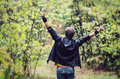 Teen boy with arms outstretched back of in woods Royalty Free Stock Images