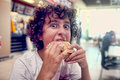 Teen boy bites his burger young with a funny expression Royalty Free Stock Photos