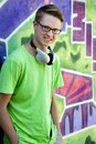 Teen boy with earphones near graffiti wall. Royalty Free Stock Image