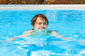Teen boy enjoys swimming in a pool cute Royalty Free Stock Photo