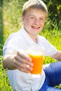 Teen boy is holding glass with juice Royalty Free Stock Photo