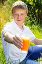 Teen boy is holding glass with orange juice Royalty Free Stock Photo