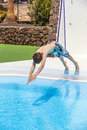 Teen boy jumping in the blue pool Stock Image