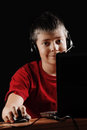 Teen boy with laptop sitting at the desk in darkness Stock Photography