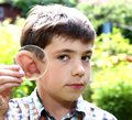Teen boy magnify  his ear with lense Royalty Free Stock Photo