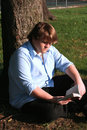Teen Boy Reading In Park Stock Photo