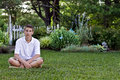 Teen boy sitting in front of garden sits on lawn appearing to me deep thought Royalty Free Stock Images
