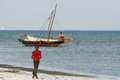 Teen boy walks on coast Indian Ocean, near fishing boat. Royalty Free Stock Photo