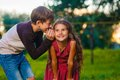 Teen boy whispering secret gossip girl child's ear Royalty Free Stock Photo