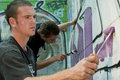 Teen boys concentrating on painting graffiti art Royalty Free Stock Photo