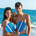 Teen couple with beach tennis rackets. Royalty Free Stock Photo
