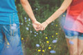 Teen couple holding hands in flower field Royalty Free Stock Photo