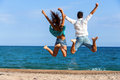 Teen couple jumping giving backs rear view of and raising arms on beach Royalty Free Stock Photography