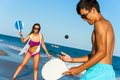 Teen couple playing smash ball beach tennis in swim wear outdoors Stock Photography