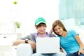 Teen friends hanging out together at home with a laptop Royalty Free Stock Image