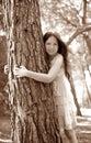 Teen girel hug a tree trunk, pine forest Royalty Free Stock Photo