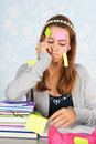 Teen girl with al lot to remember sitting at desk homework for school and having a Royalty Free Stock Photography