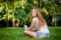 Teen girl with book reader young woman reading on electronic outdoor rear view Royalty Free Stock Images