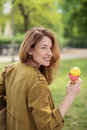 Teen girl carrying her bag while holding ice cream pretty in brown jacket on cone and looking at the camera Stock Photography