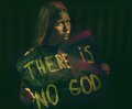 Teen girl with dirty face holding banner with a text there is no god atheistic concept Royalty Free Stock Image