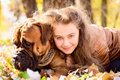 Teen girl and dog bullmastiff lie in the park in autumn Royalty Free Stock Photos