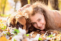 Teen girl and dog bullmastiff lie in the park in autumn Stock Image