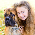 Teen girl and dog bullmastiff in the park in autumn Royalty Free Stock Photo