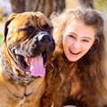 Teen girl and dog bullmastiff in the park in autumn Royalty Free Stock Image