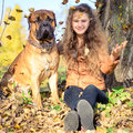 Teen girl and dog bullmastiff sit in the park in autumn Stock Image