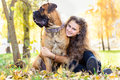 Teen girl and dog bullmastiff sit in the park in autumn Royalty Free Stock Photography