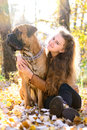 Teen girl and dog bullmastiff sit in the park in autumn Stock Images