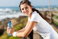 Teen girl exercise beautiful with water bottle after morning at beach Royalty Free Stock Images