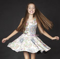 Teen girl fashion in a dress against a black studio background Royalty Free Stock Images