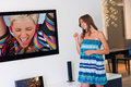 Teen girl in front of tv attractive holding big screen Royalty Free Stock Photography