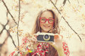 Teen girl in glasses with vintage camera near blossom tree Royalty Free Stock Photo