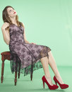Teen girl green screen elegant wearing a purple dress and red heels sitting on a bench against a background chroma key Stock Photo