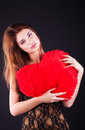 Teen girl with heart pillow over the black Royalty Free Stock Images