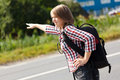 Teen girl hitch hiking on the road Royalty Free Stock Images