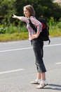 Teen girl hitch hiking on the road Royalty Free Stock Photo