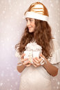 Teen girl holding christmas gift portrait of nice in hands festive box and looking on the side little santa claus helper time Stock Images