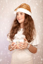 Teen girl holding christmas gift portrait of nice in hands festive box and looking on the side little santa claus helper time Royalty Free Stock Photography