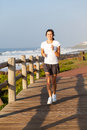 Teen girl jogging healthy by the beach in the morning Stock Image