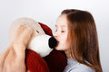 Teen girl kissing a toy dog ​​in the nose Royalty Free Stock Image