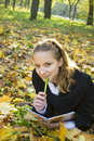 Teen girl lies in autumn park with her diary Royalty Free Stock Photos