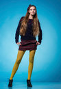 Teen girl with long straight hair beautiful posing on blue background Stock Images