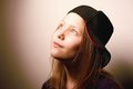 Teen girl looking up and smiling cute dreamy in cap Royalty Free Stock Photography