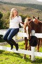 Teen girl loves her horses a caucasian blond sitting on top of a white picket fence dressed in riding gear stroking a mahogany Stock Photo